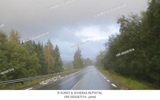 POV shot of a car driving on a country road on a rainy day. The sun shines while it's still raining. Noraström, Västernorrlands Län, Sweden