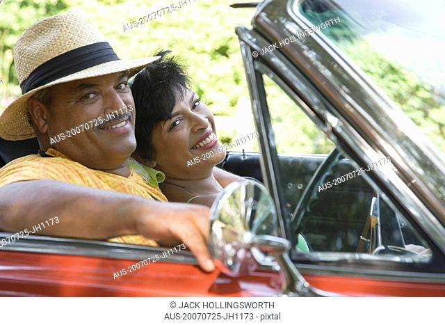 Portrait of a senior man and a mature woman sitting in a convertible car