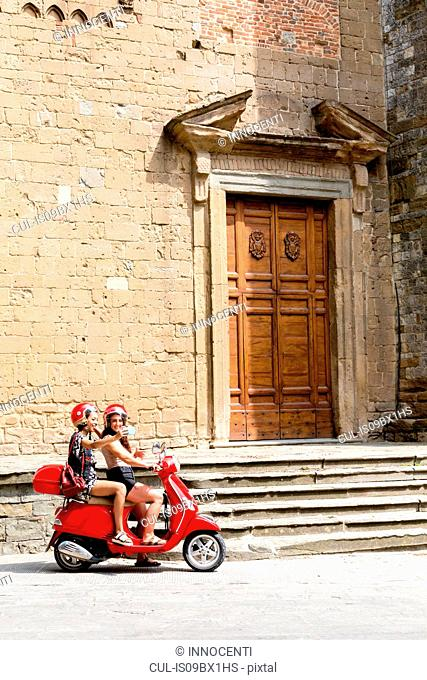 Friends taking selfie on scooter by church entrance, Città della Pieve, Umbria, Italy