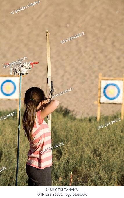 Tourist doing archery on Mingsha Mountain, Dunhuang, China