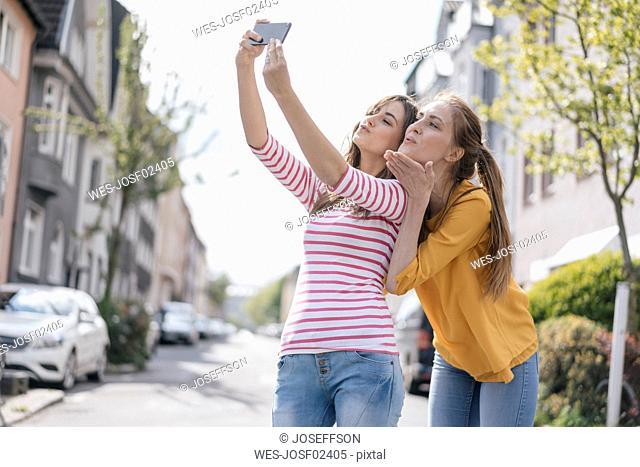 Girlfriends taking selfie in the city