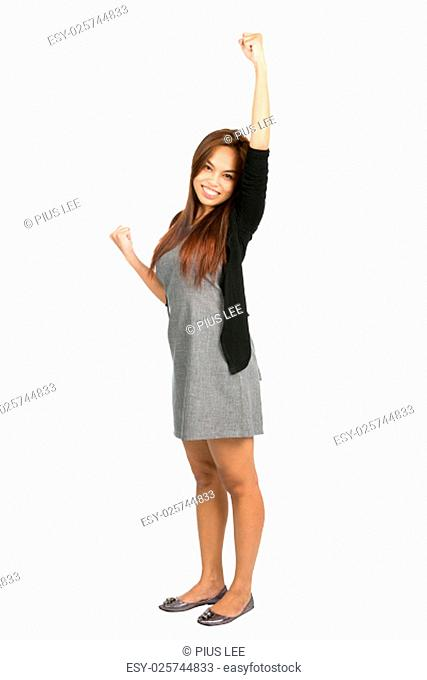 Cute young Asian girl in gray dress, black sweater raising her arm, pumping her fist, quietly celebrating, cheering a goal