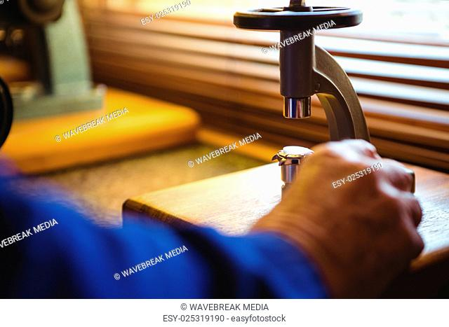 Hand of horologist using a microscope