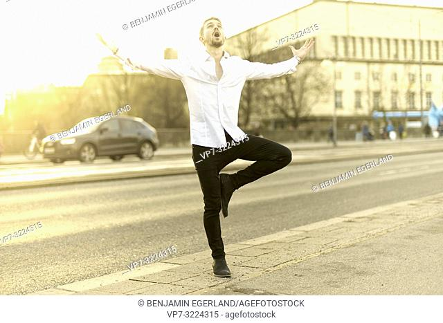 young man screaming at street with open arms, balancing on one feet, in Munich, Germany