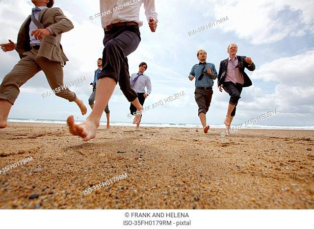 Businessmen running on beach