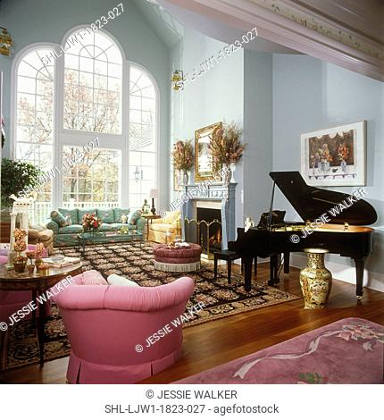 LIVING ROOM - Two story traditional Living Room with large palladian style window. Light blue walls, grand paino, fireplace, large patterned area rug
