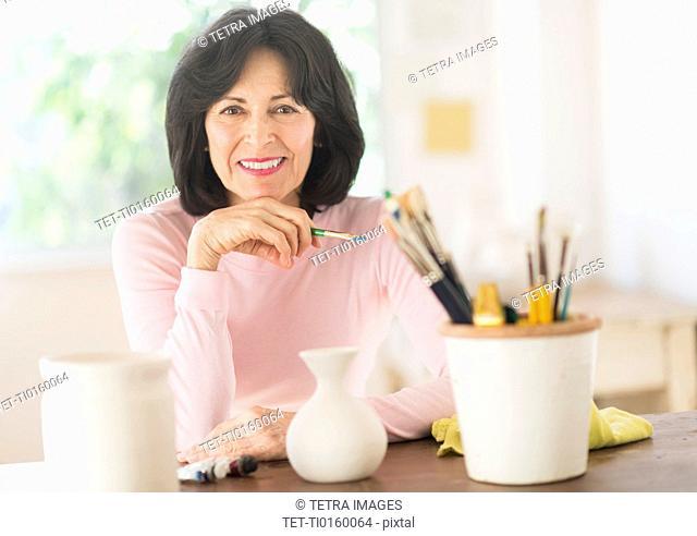Senior woman painting handmade pottery