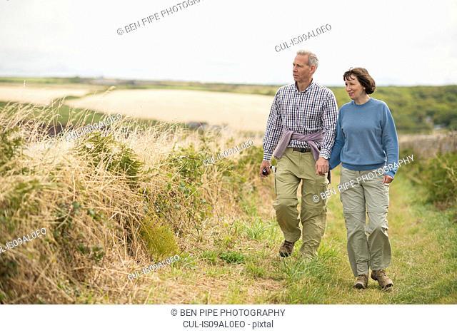 Couple walking, Coast Path near Marloes, Pembrokeshire Coast National Park, Wales, UK