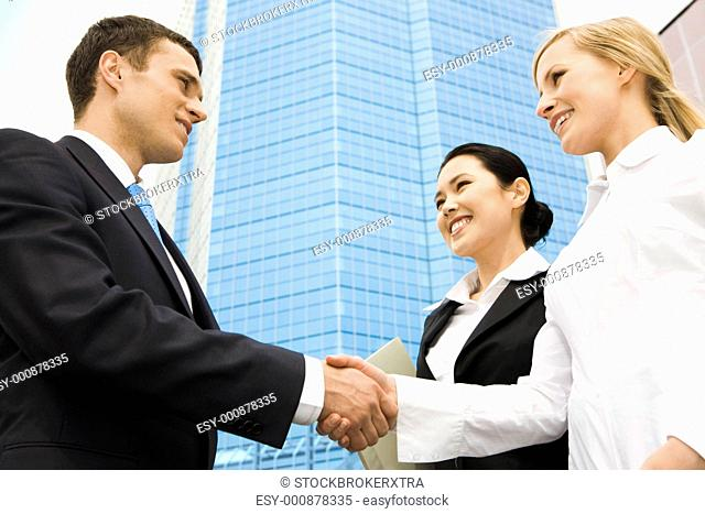 Image of successful partners handshaking at background of modern building