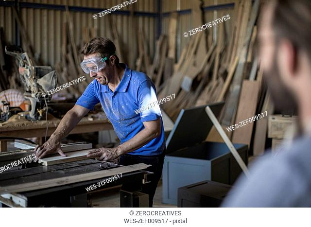Carpenter working with saw in workshop