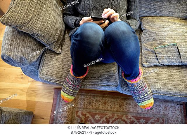 Closeup of a woman sitting on fitness casual and relaxed on a couch, manipulating a cell phone. Buckden, Skipton, Yorkshire Dales, England, UK, europe