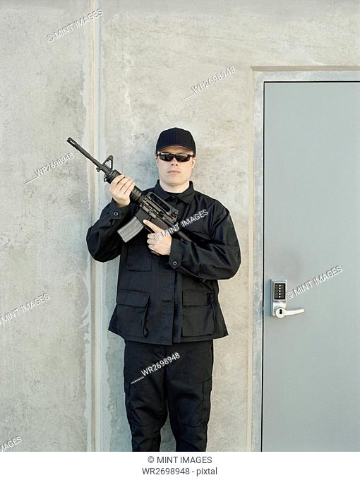 Man wearing special forces uniform and holding high powered semi-automatic rifle, guarding doorway