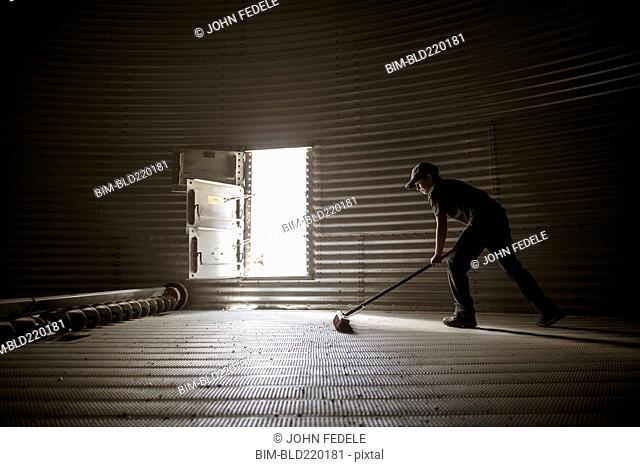 Caucasian boy sweeping empty silo