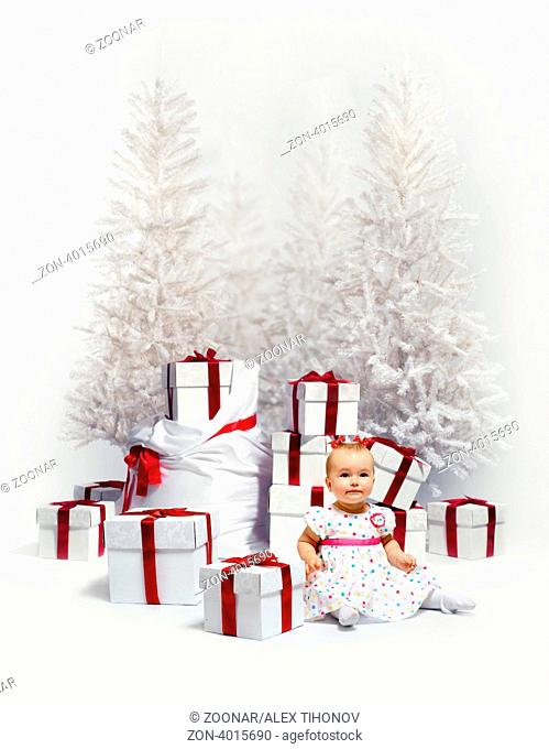 Adorable baby girl over christmas trees and heap of gift boxes background