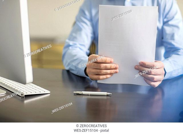 Businessman sitting at office desk with documents and ballpen