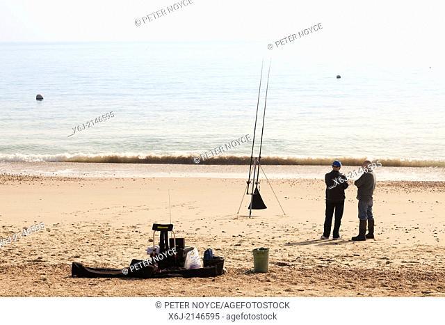 Two men sea fishing from beach