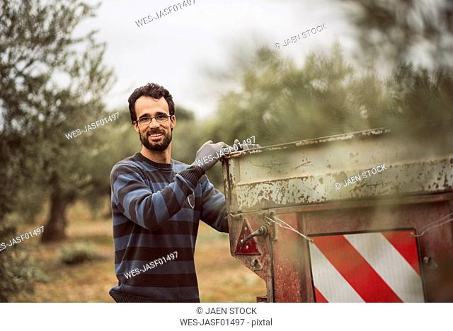 Spain, portrait of smiling man working in olive grove