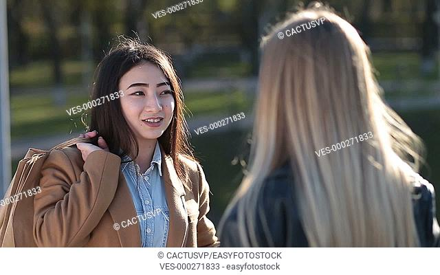 Cheerful asian girl gossiping with female friend
