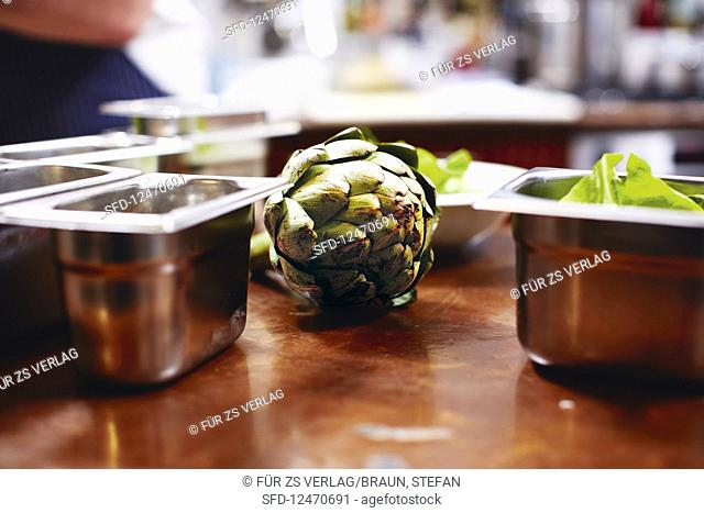 Artichokes between metal containers in a kitchen
