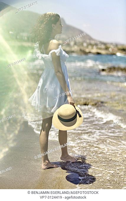 woman on beach, sunlight, reflections, enjoying summer, in Hersonissos, Crete, Greece