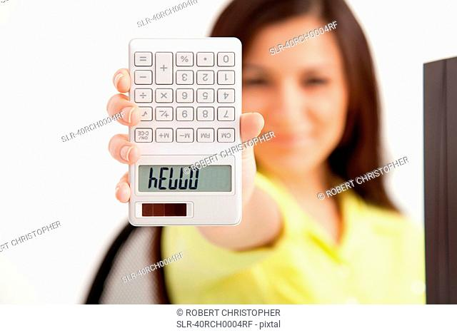 Businesswoman writing on calculator