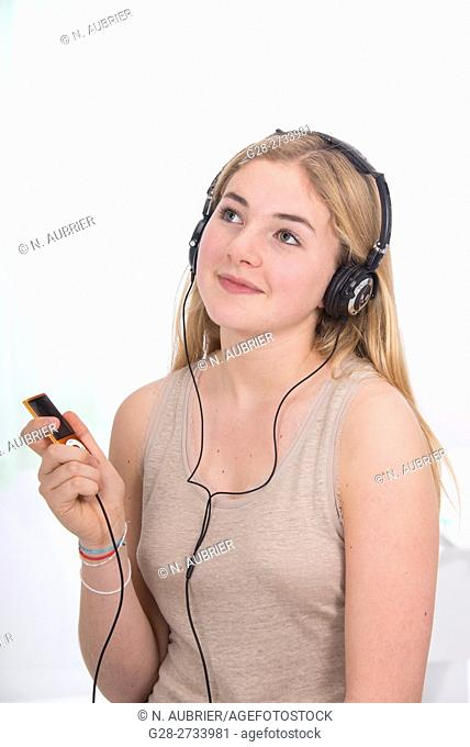 Portrait of happy blond teenage girl holding her i-pod in one hand and listening to music, at home