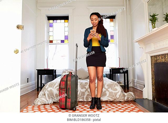 African American woman using cell phone in bedroom