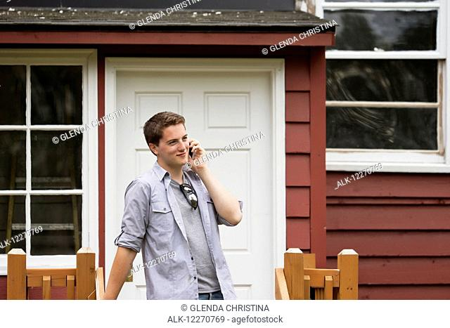 Teenage boy on a smart phone at the Knik Goose Bay Museum in Wasilla, Southcentral Alaska, Summer