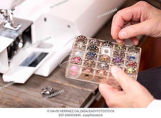 Close up on seamstress hands choosing threads for electrical sewing machine