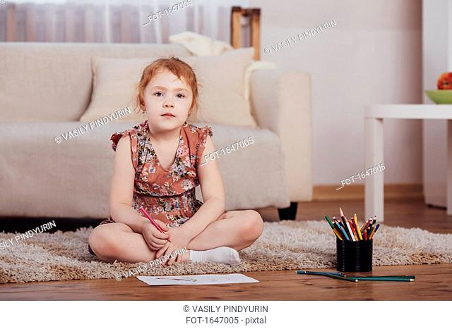Portrait of smiling girl drawing while sitting on carpet in living room at home