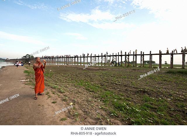 Orange robed monk photographing people crossing U Bein's Bridge, supported by 984 teak posts over Thaumthaman Lake, Mandalay, Myanmar (Burma), Asia