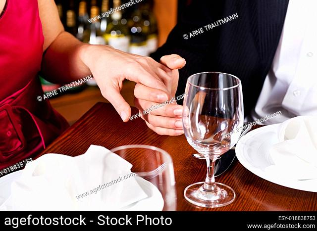 Paar hält sich die Hände auf Restauranttisch