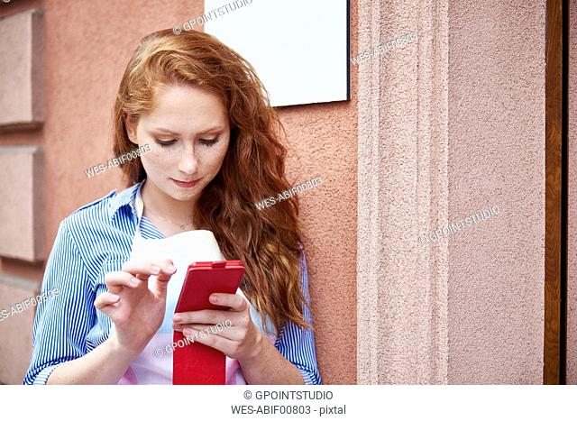 Young woman using a cell phone during a work break