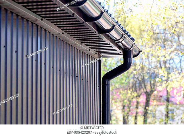 brown siding wall with plastic rain gutter and drainpipe