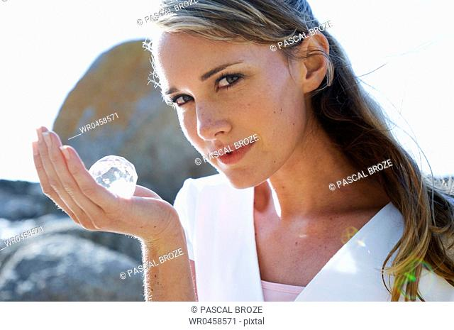 Close-up of a mid adult woman with a crystal ball in her hand