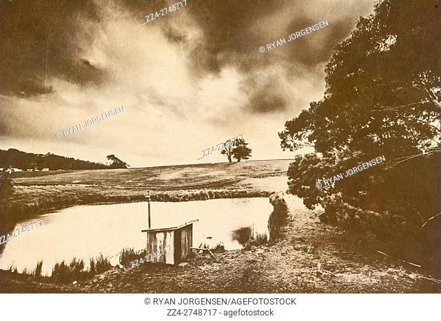 Small shelter near edge of calm pond in moody landscape of rural scene in Camena, North Tasmania, Australia