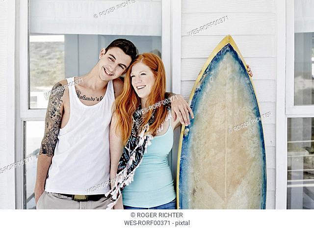 Happy young couple with surfboard standing in front of beach house