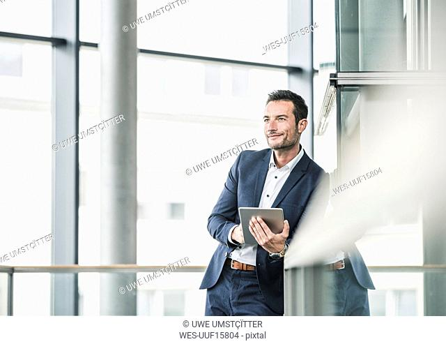 Businessman standing in office building, using digital tablet
