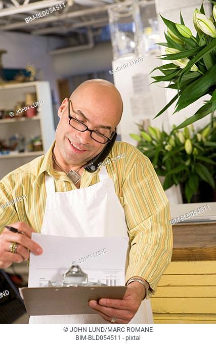 Hispanic male clerk talking on telephone