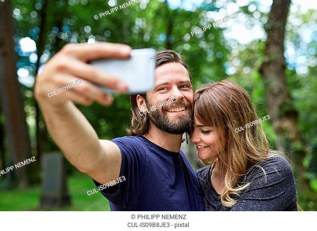 Couple taking selfie in park