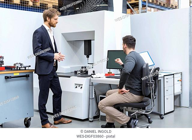 Two men talking at machine in modern factory