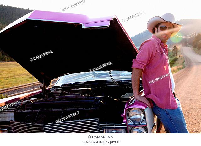 Man leaning against vintage car with hood up