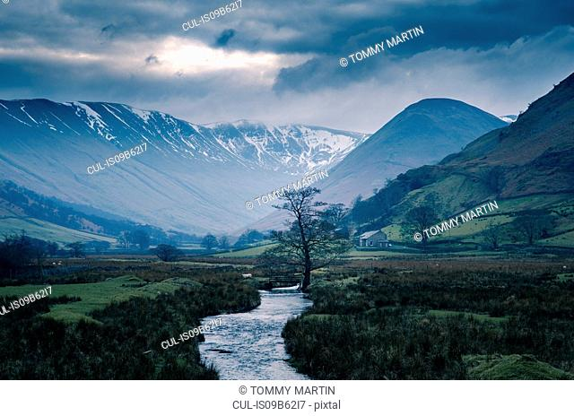 Storm clouds over snow capped mountains at Martindale, The Lake District, UK
