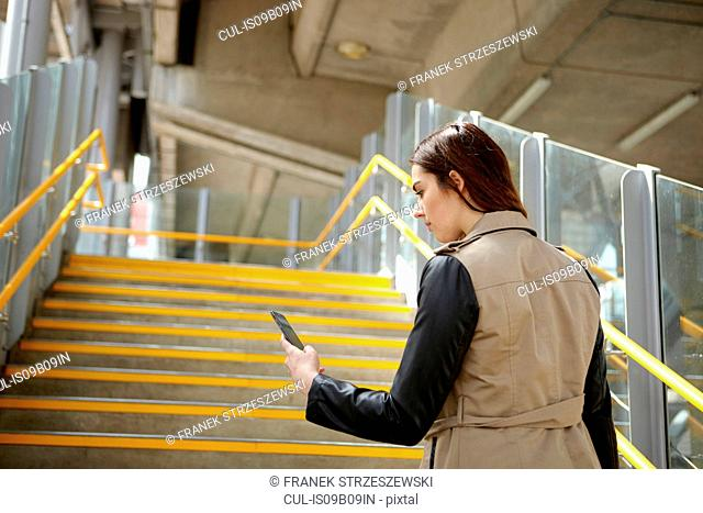 Rear view of young businesswoman reading smartphone texts on stairway, London, UK