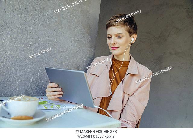 Woman with tablet and earbuds in a cafe