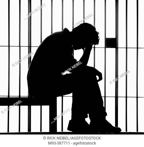 Sitting man. head in hand, silhouetted against jail bars