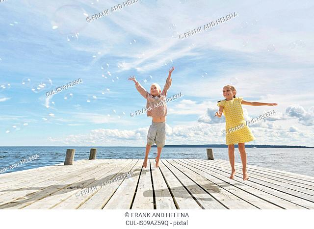 Two young friends on wooden pier, jumping to reach bubbles