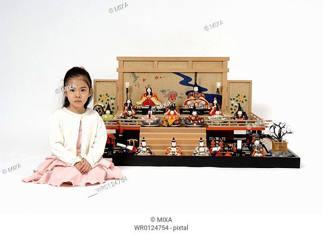 Girl sitting in front of hinamatsuri dolls