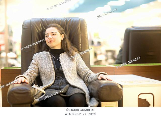 Portrait of confident young woman resting in a leather chair in a shop