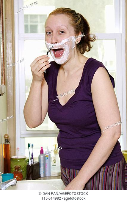 Woman in bathroom shaving like a man for fun